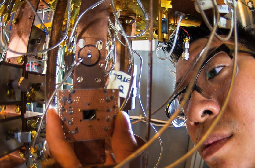 The cutting-edge science of quantum computing requires nanoscale precision mixed with the tinkering spirit of home electronics. Researcher Jerry Chow is here shown fitting a circuitboard in the IBM quantum research lab.