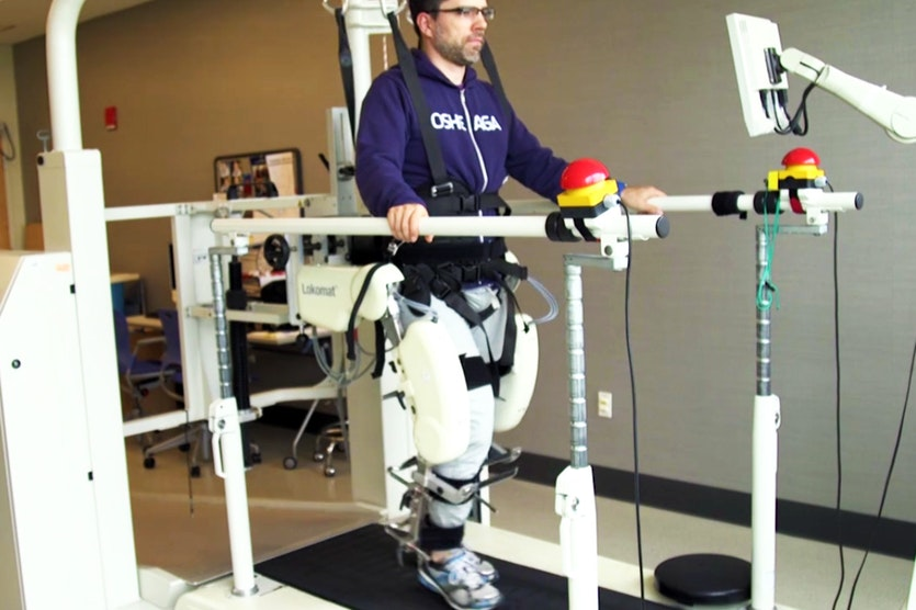 A man practising walking with the aid of robotic exoskeleton legs.