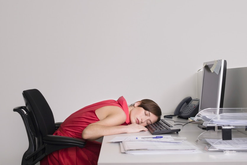 A woman asleep at her desk.