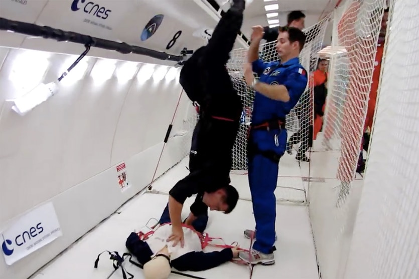 An astronaut demonstrates a handstand CPR technique in a simulated low-gravity environment.