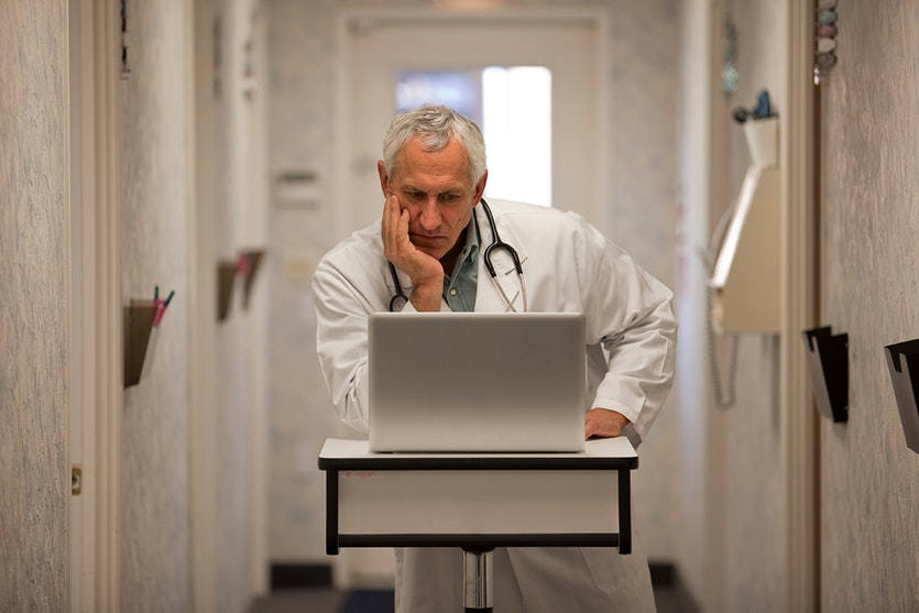 A perplexed doctor stares a computer.