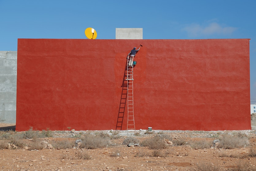 A man painting a wall red against a blue sky.