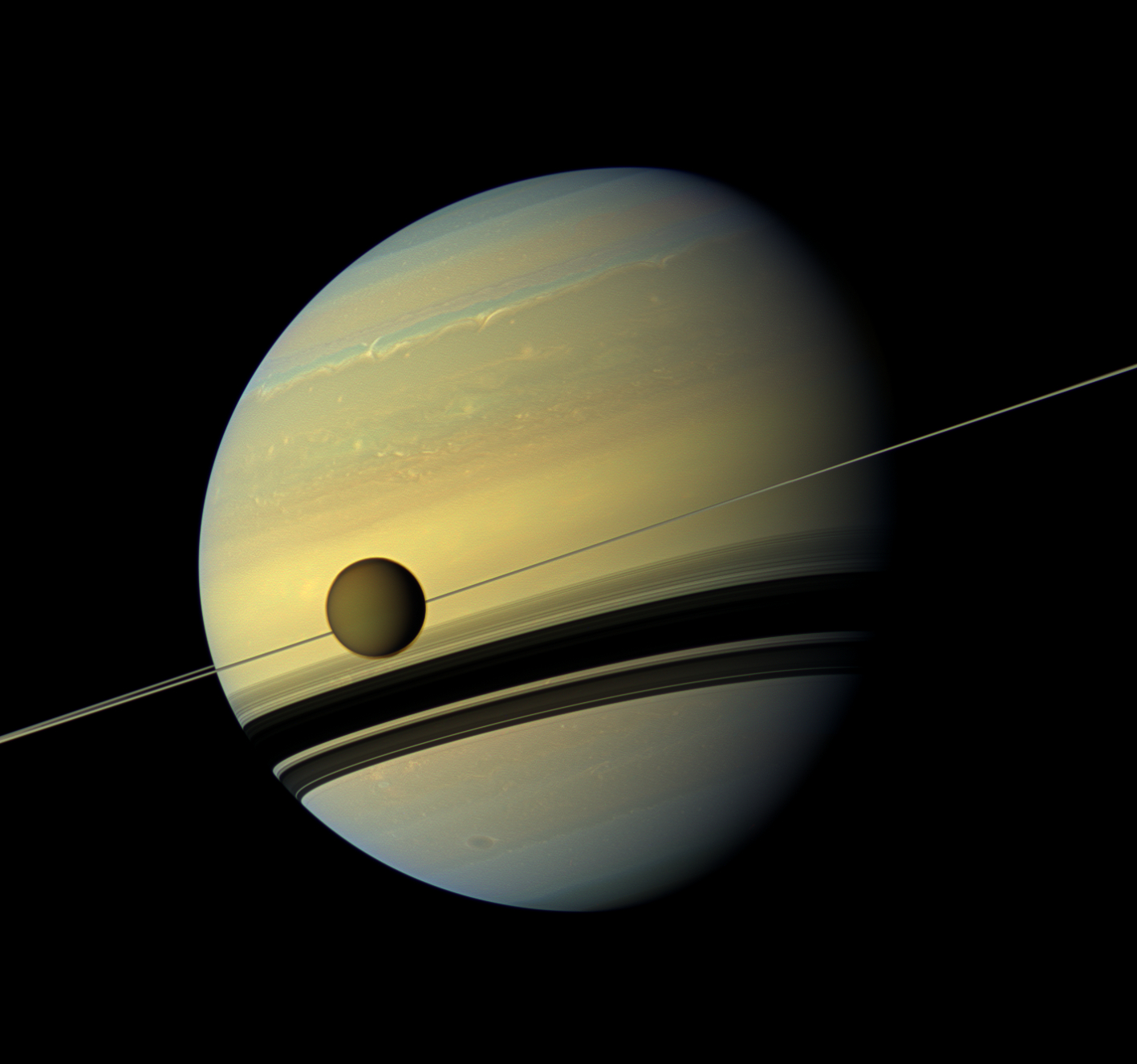 Titan, Saturn's largest moon, with Saturn in the background.