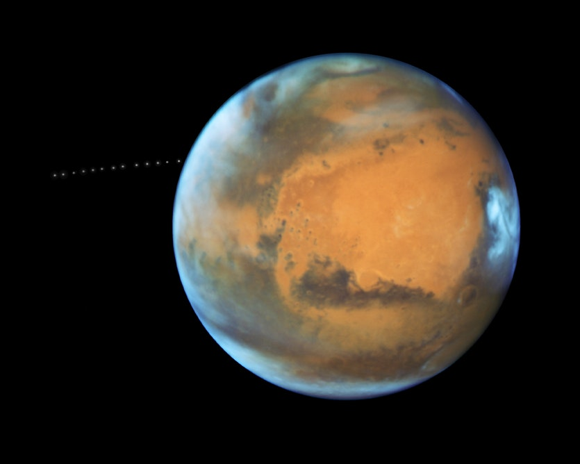 This composite image made from 13 photos taken over 22 minutes shows Phobos emerging from behind Mars.