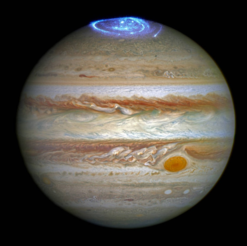 A composite image from the Hubble Space Telescope showing Jupiter in visible light and its aurora in ultraviolet.