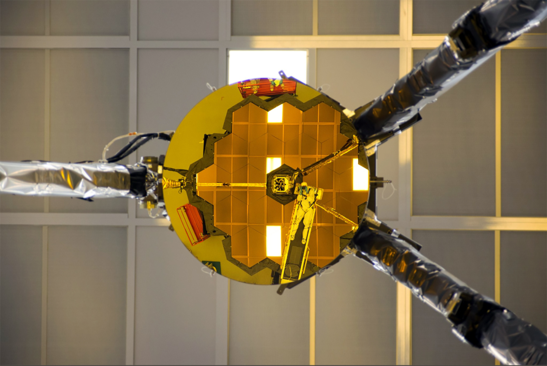 Optical engineer Larkin Carey is reflected in the James Webb Space Telescope's secondary mirror, as he photographs the line of sight for hardware used during an important test of the telescope's optics.
