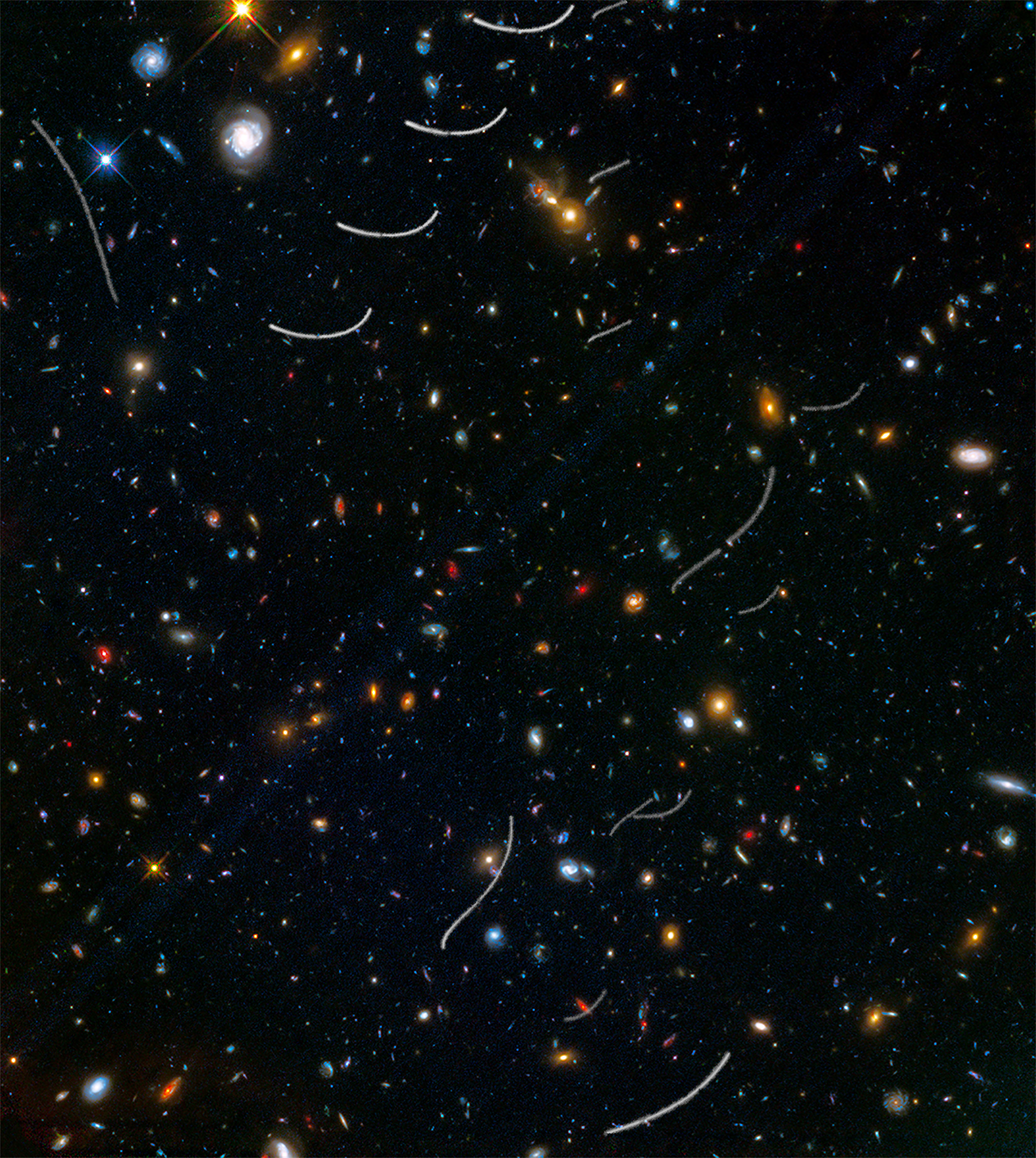 This Hubble photo of a random patch of sky is part of a survey called Frontier Fields. It contains thousands of galaxies, including massive yellowish ellipticals and majestic blue spirals. Much smaller, fragmentary blue galaxies are sprinkled throughout the field. The reddest objects are most likely the farthest galaxies. Asteroid trails appear as curved or S-shaped streaks. Asteroids appear in multiple Hubble exposures that have been combined into one image.