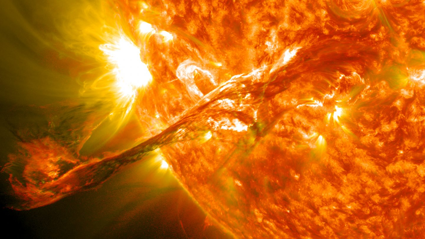 A massive filament of plasma bursts forth from the Sun.