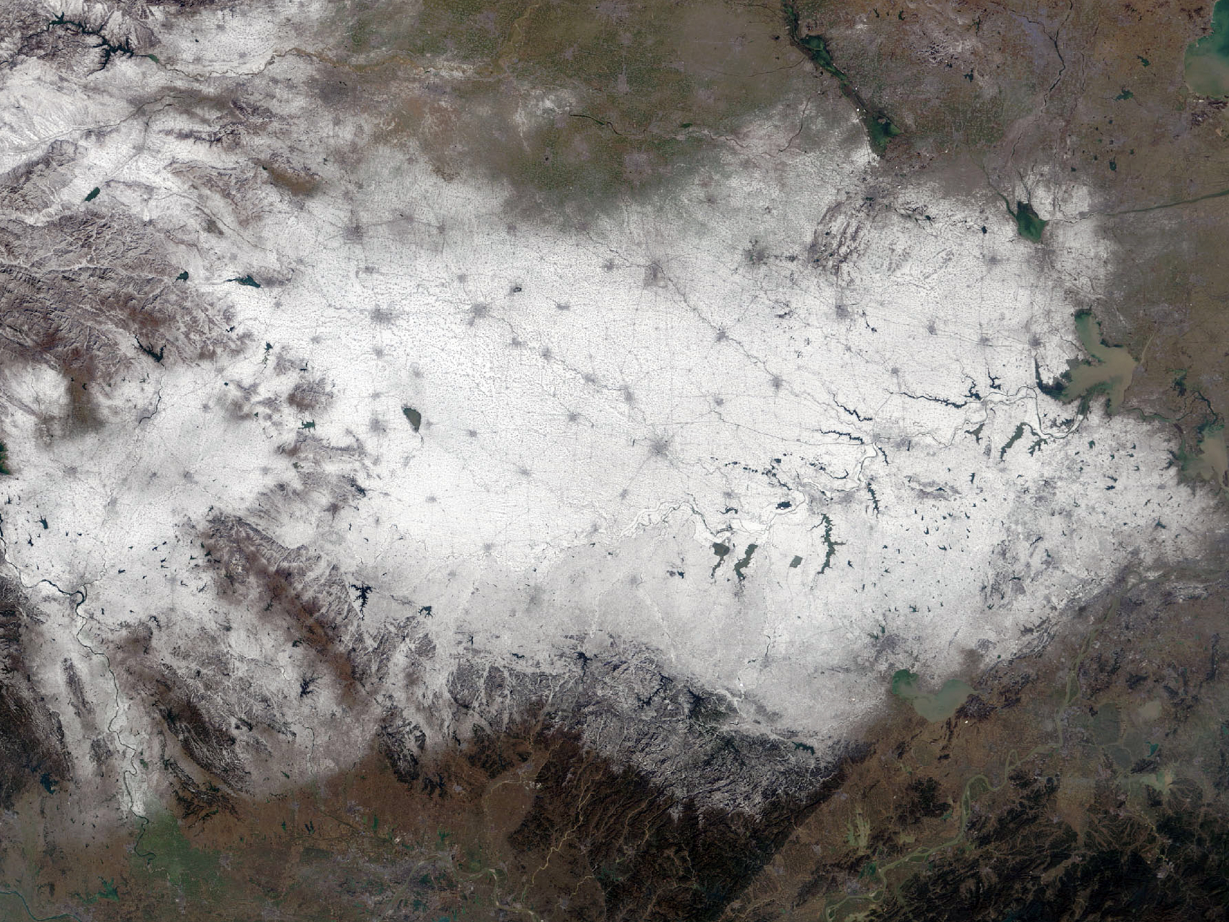Snowfall in central China. Dark grey spots and lines are cities and roads.