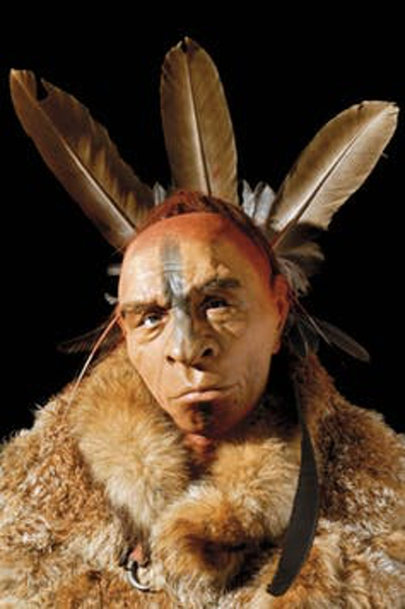 Reconstruction of a Neanderthal man wearing body paint and eagle feathers.