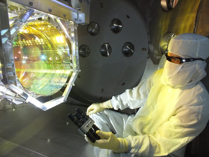 Before sealing up the chamber and pumping the vacuum system down, a LIGO optics technician inspects one of LIGO's core optics (mirrors) by illuminating its surface with light at a glancing angle.