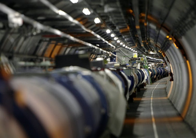 View of the LHC in its tunnel at CERN (European particle physics laboratory) near Geneva, Switzerland. The LHC is a 27-kilometre-long underground ring of superconducting magnets housed in this pipe-like structure, or cryostat. The cryostat is cooled by liquid helium to keep it at an operating temperature just above absolute zero. It will accelerate two counterrotating beam of protons to an energy of 7 tera-electron volts (TeV) and then bring them to collide head-on. Several detectors are being built around the LHC to detect the various particles produced by the collision.