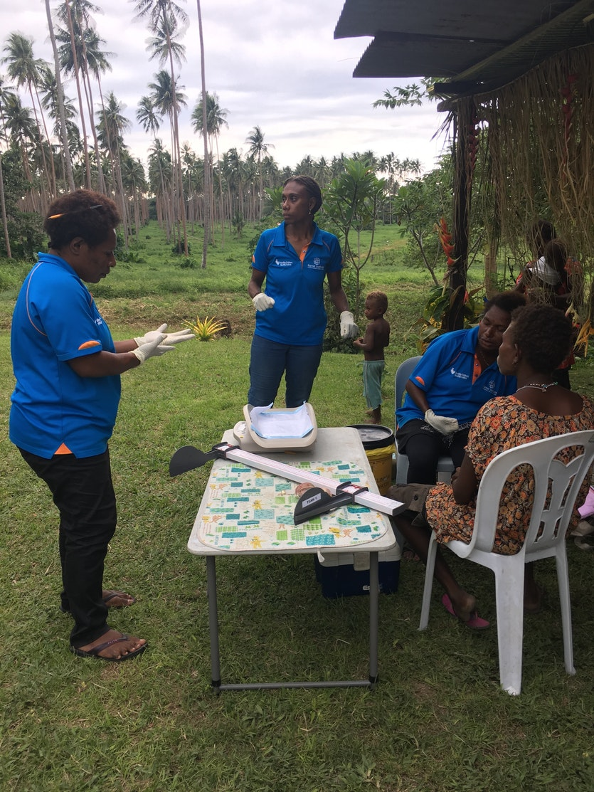 Members of the Burnet team get ready to take a baby's vital statistics in a village near Tovarur plantation in East New Britain.