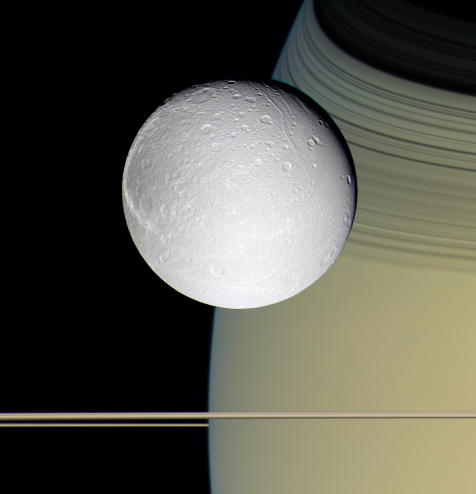 The moon Dione seen with Saturn and Saturn's rings.