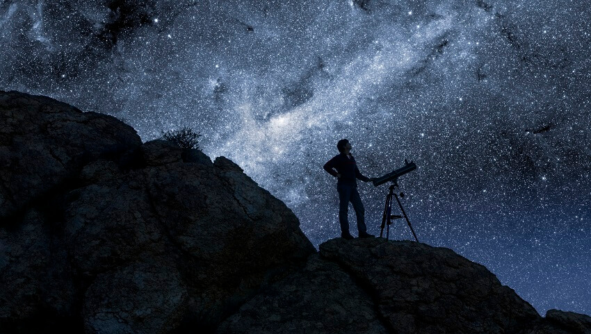 man looking at stars next to telescope