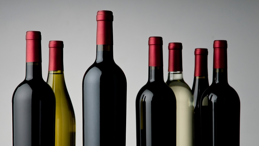Generic alcohol and wine bottles against grey background