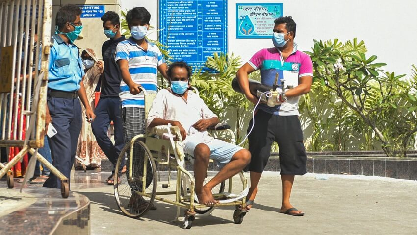 A covid-19 patient in a wheel chair with an oxygen cylinder. One man is pushing the chair and another is holding the oxygen tanks. A government official walks behind them