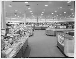 A black and white photo. and isle with cabinets on each side. Lights are lined on the roof.