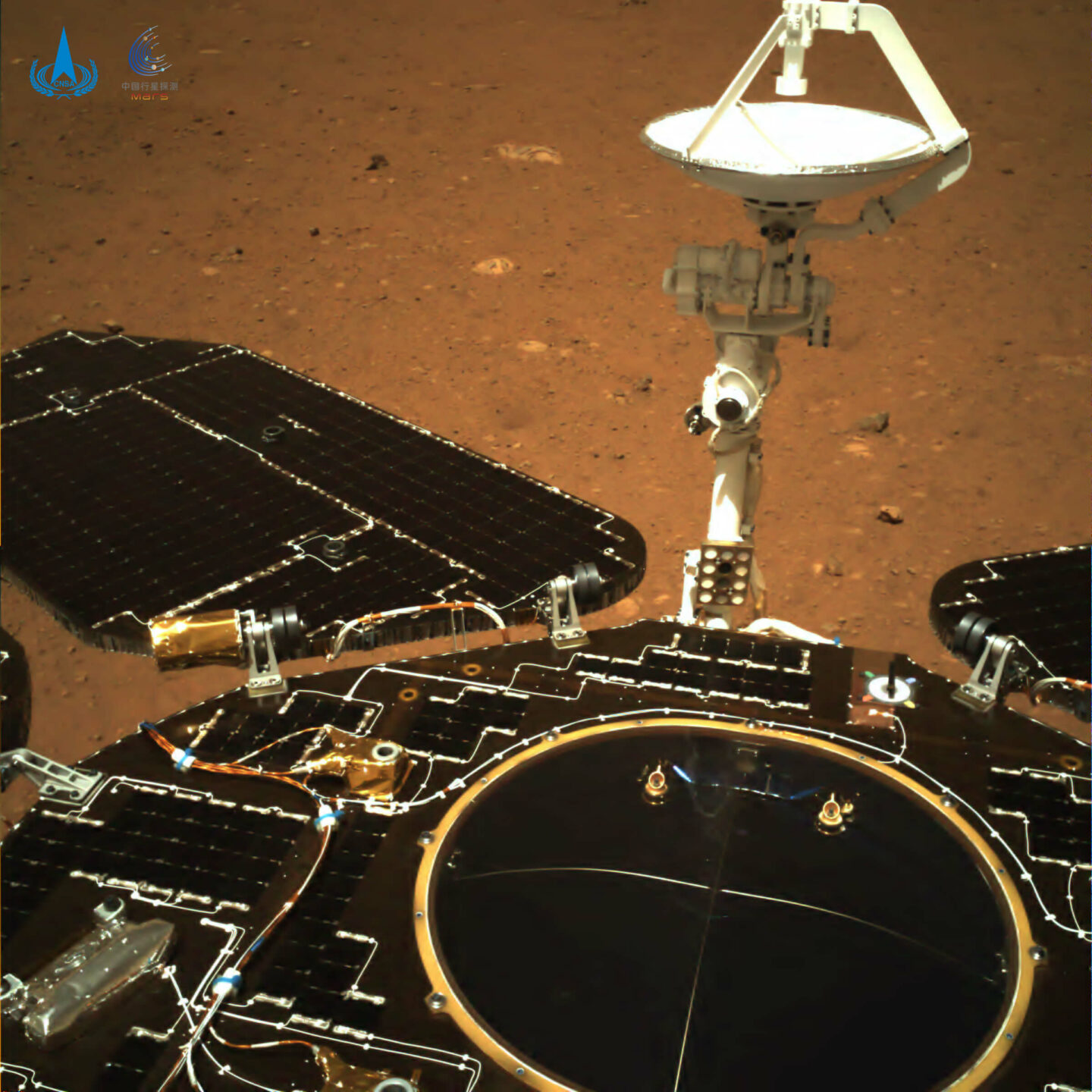 A machine with wings and a satellite. It is black. There is red soil in the background