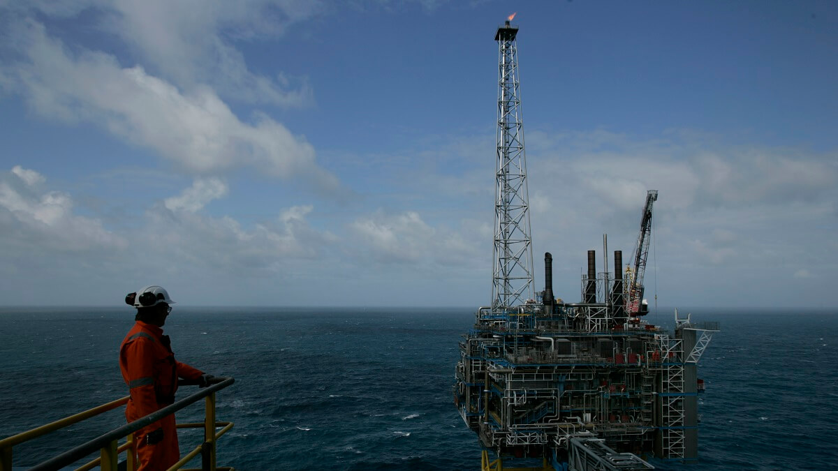 Photo of a worker looking at the sleipner carbon capture unit, on the sea in norway.