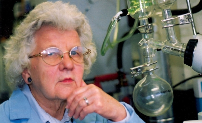 A woman with white hair sitting next to a chemistry apparatus