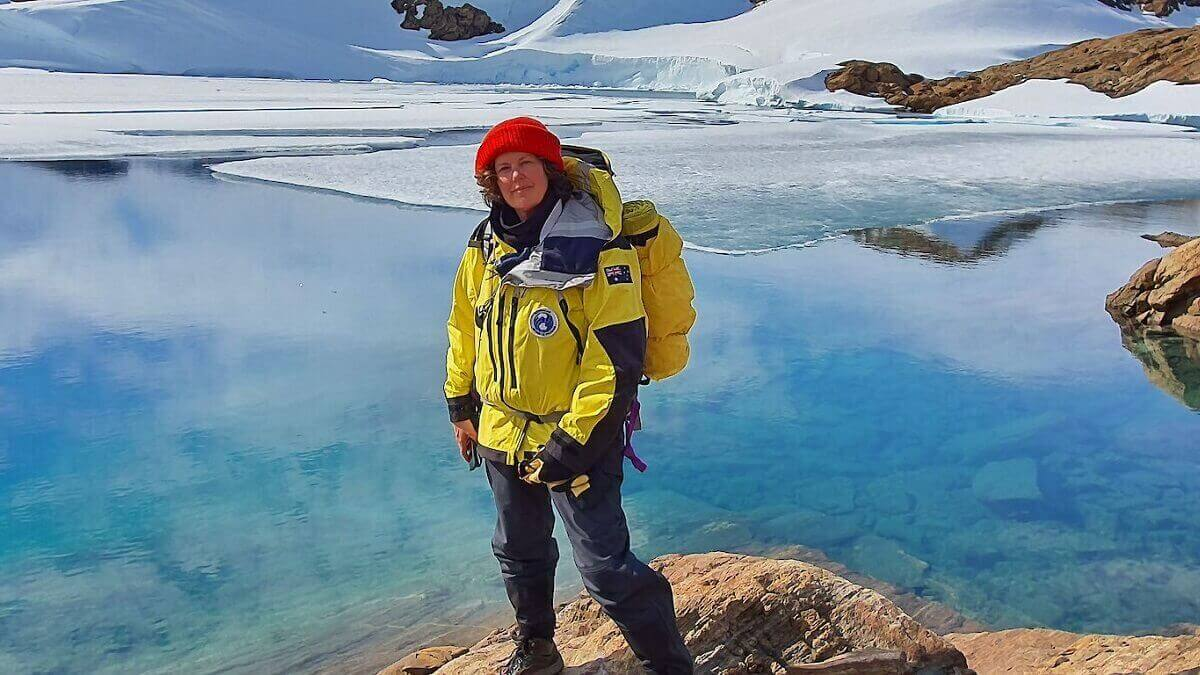 Person in bright yellow jacket stands on a rock in front of icy landscape